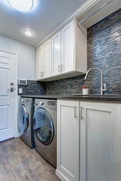White laundry room boasts white shaker cabinets