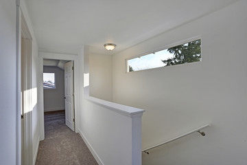 Photo of a White hallway with a staircase