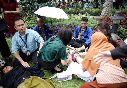 Injured people are treated outside the Indonesia Stock Exchange building following reports of a collapsed structure inside the building in Jakarta