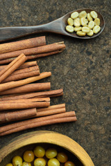 fresh coffee beans in wooden bowl with cinnamon for background