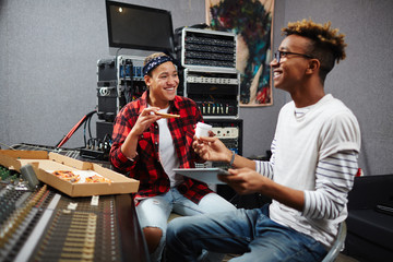 Two sound operators having pizza and coffee in their record studio at lunch break