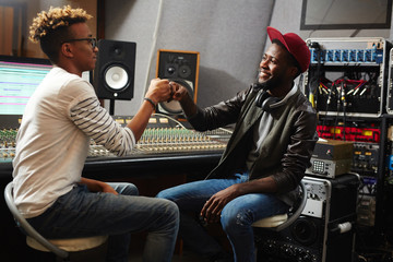 Two happy young musicians making punch bump while working in studio of sound recording