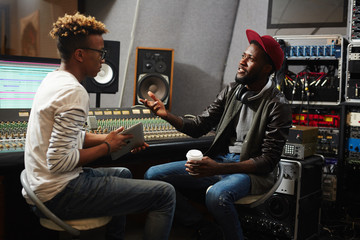 Young rapper explaining sound recording operator his ideas about how his music should sound