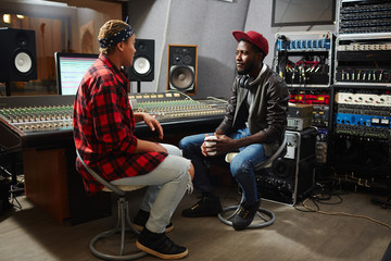 Operator of audio studio having talk with young musician about releasing new album