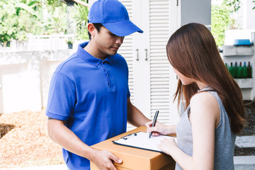 Woman putting signature in clipboard on cardboard box with delivery man
