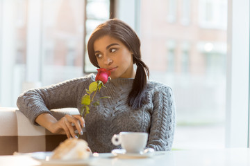 Young woman in grey sweater smelling fresh red rose while spending time in cafe