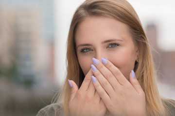 young woman holding her hands in front of her mouth