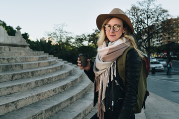 Sunny autumn day, backlight. Young attractive woman tourist in hat, eyeglasses and with backpack stands on city street,drinks coffee. Hipster girl walks, looks at sights. Vacation, adventure, trip.