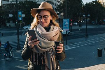 Sunny autumn day. Young attractive woman tourist in hat and eyeglasses stands on city street, uses smartphone and drinks coffee. Hipster girl is looking for road. Vacation, adventure, trip.