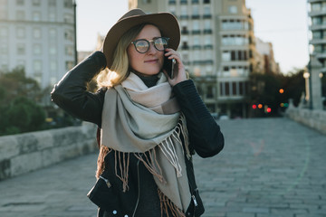Sunny autumn day, backlight. Young attractive woman travels in hat and eyeglasses stands on city street, talking on cell phone, smiling, holding her hat. Hipster girl walks. Vacation, adventure, trip.
