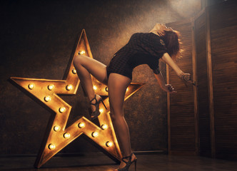 sexy young woman on the background of a star with lamps