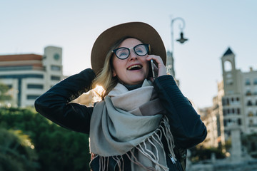 Sunny autumn day, backlight. Young attractive woman travels in hat and eyeglasses stands on city street, talking on cell phone, smiling, laughing. Hipster girl walks. Vacation, adventure, trip.