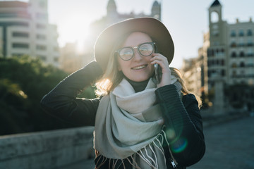 Sunny autumn day, backlight. Young attractive woman tourist in hat and eyeglasses stands on city street, talking on cell phone, smiling, laughing. Hipster girl walks. Vacation, adventure, trip.