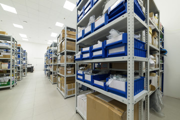 Industrial warehouse. White metal racks with blue plastic trays and cardboard boxes installed in them.