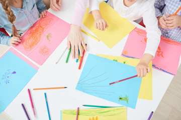 Top view of colorful paper, crayons and human hands during discussion of drawn pictures