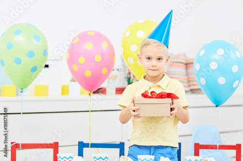 Adorable Boy Holding Box With Birthday Gift During Party In Kindergarten
