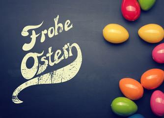 Frohe Ostern auf einer Tafel mit bunten Plastik Ostereiern, Grußkarte