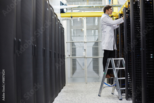 Young bitcoin miner in whitecoat repairing storage hardware in
