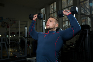 Strong muscular young man in sportswear exercising with dumbbells