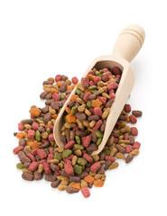 Heap of dry pet food in wooden scoop