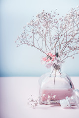 Herbal cosmetic or wellness concept. Glass jar with pink lotion and flowers at pastel color background, top view