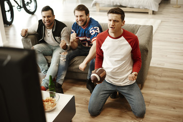 Male friends watching American football.