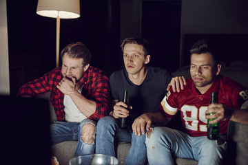 Men friends watching american football in the evening.