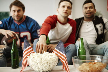 Unrecognizable football fans snacking at home