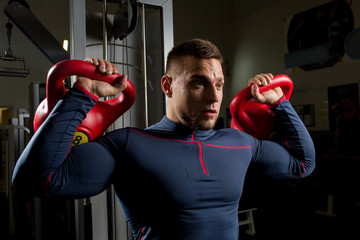 Strong muscular athlete lifting heavy kettlebars during physical training