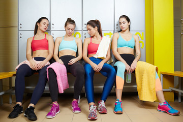 Row of sporty girls in activewear having rest in dressing-room after training