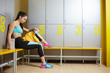 Tired young sportswoman with towel and plastic bottle of water sitting on bench in dressing room