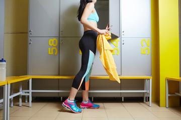 Sportswoman with towel opening door of cabinet in changing room