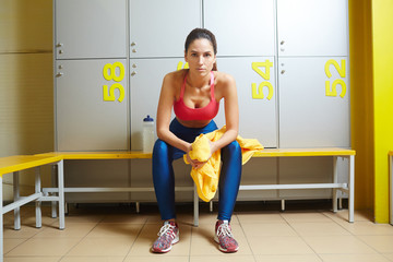 Serious young female in activewear holding towel while sitting on bench in changing room