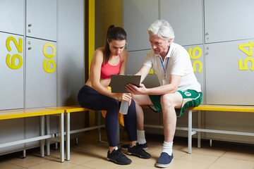 Mature trainer showing one of his trainees her results and discussing them