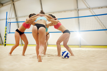 Group of young volleyball players standing in embrace on sandy fiels during game