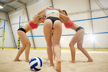Young fit volleyball players making circle while standing on sand during training