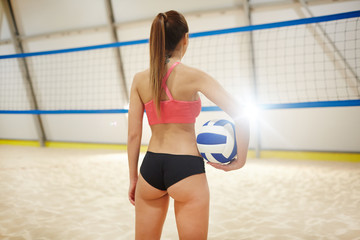 Young volleyball player with ball standing on sandy field in gym