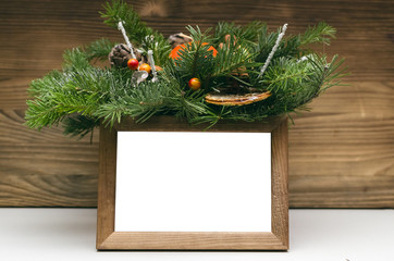 Empty blank photo frame with copy space and Christmas tree branches on burnt wooden wall background.