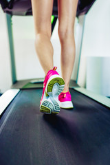 Woman runs. Beautiful athletic female feet in colorful sneakers on a treadmill.