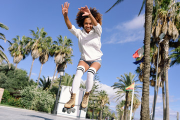 Black woman, afro hairstyle, on roller skates jumping near the beach.