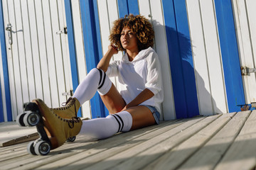 Young black woman on roller skates sitting near a beach hut.