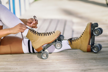 Close-up of black girl sitting on wooden floor puts on skates.
