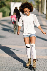 Black woman on roller skates rollerblading in beach promenade with palm trees