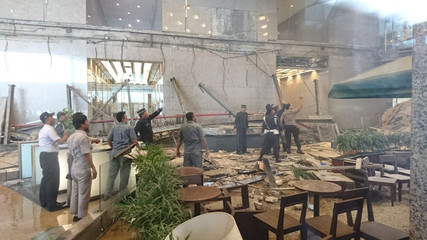Workers and security examine the damage after a mezzanine floor collapsed at the Indonesia Stock Exchange building in Jakarta