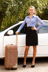 Beautiful young woman standing by the white car with big suitcase