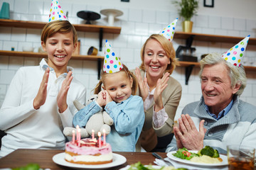 Happy family members clapping their hands while little girl going to blow candles on birthday cake