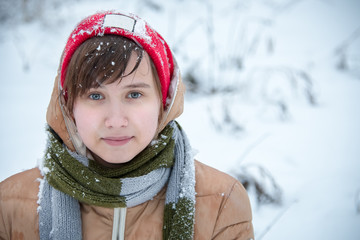 Winter portrait of a girl that eats snow. Blizzard. Close-up. A blurred background. Nikon D750