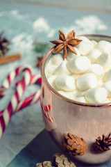 Hot chocolate with marshmallows, cinnamon and anise, served with christmas decoration. Selective focus. Toned image.