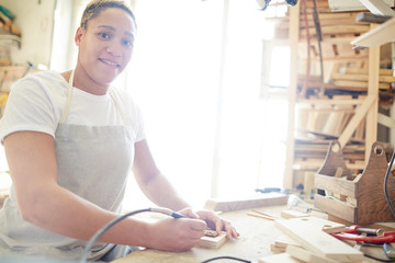 Young woman with pyrographic machine looking at camera during work