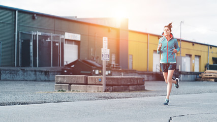 Young sporty woman jogging alone in the urban area